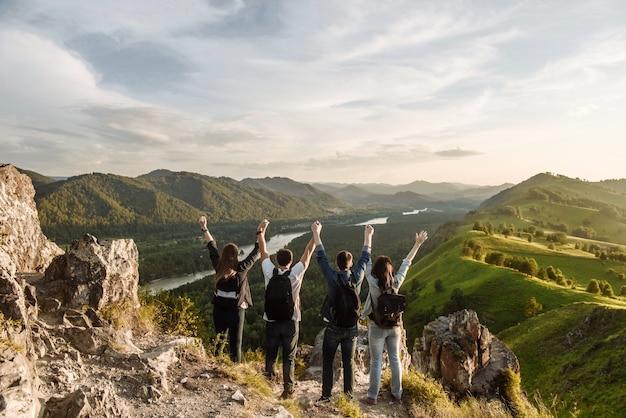Un grupo de excursionistas de cuatro personas con mochilas en las montañas.