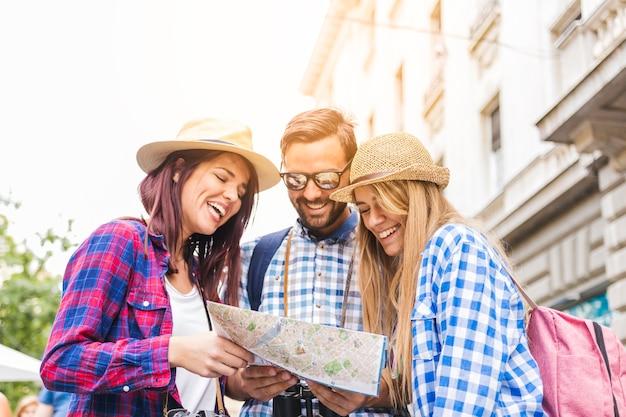 Grupo de excursionistas masculinos y femeninos felices que buscan ubicación en el mapa