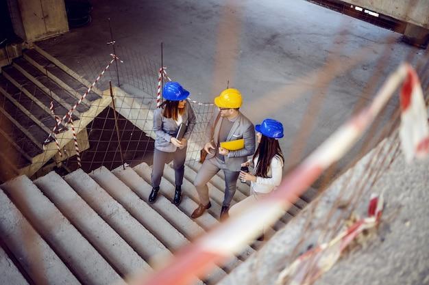 Grupo de exitosos arquitectos jóvenes e innovadores subiendo las escaleras y hablando de objetos. edificio en interior de proceso de construcción.