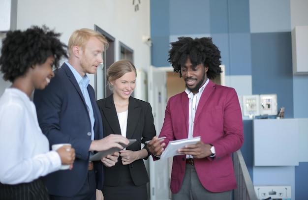 Grupo de exitosos socios comerciales diversos que tienen una reunión de negocios en una oficina moderna