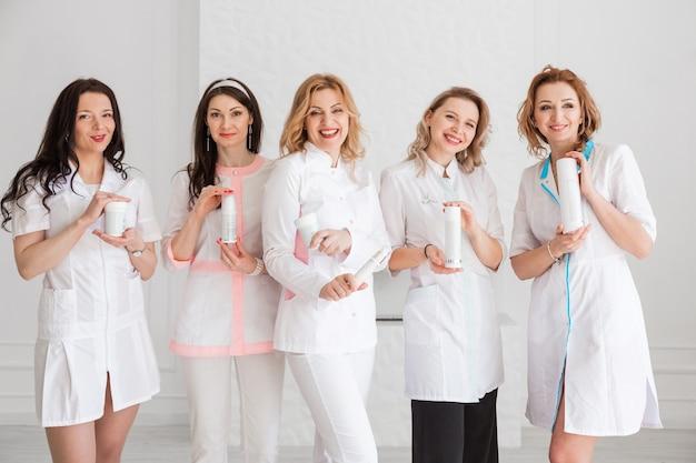 Un grupo de felices hermosas doctoras, enfermeras, pasantes, asistentes de laboratorio en uniforme blanco posando tubos de crema contra el fondo de una pared blanca.