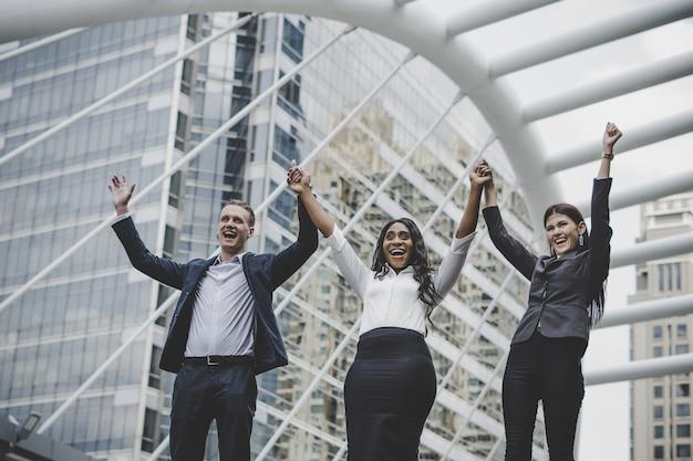 Grupo de felices jóvenes empresarios con las manos en el aire de éxito en sus planes.