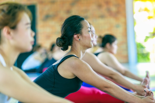 Grupo femenino asiático de la aptitud que hace actitud de la yoga del namaste en fila en la clase de la yoga. enfoque selectivo