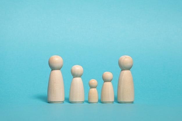 Grupo de figuras de madera sobre fondo azul concepto de familia