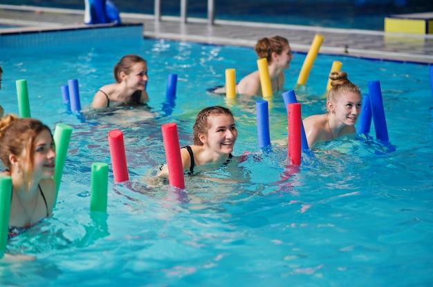 Grupo de fitness de chicas haciendo ejercicios aeróbicos en la piscina en el parque acuático.
