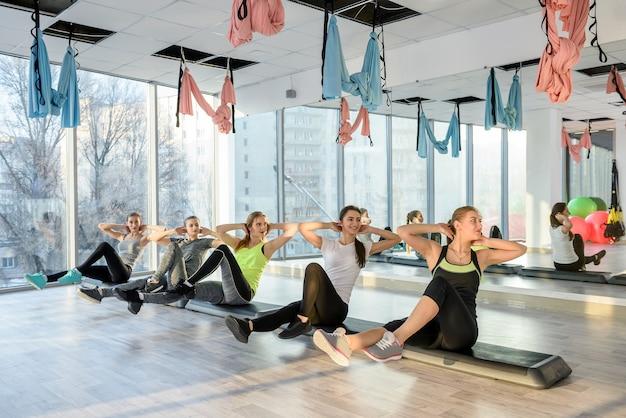 Grupo de fitness entrenamiento de los músculos del vientre en gimnasio