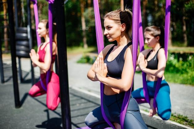 Grupo de fitness haciendo yoga en el parque en un día soleado
