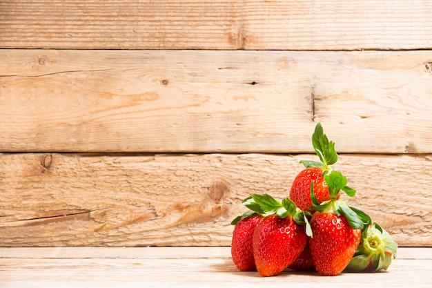 Grupo fresa roja madura en mesa de madera