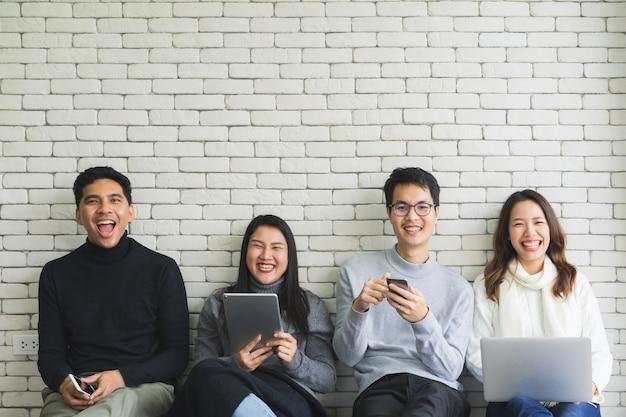 Grupo de generación milenaria que sostiene dispositivos de dispositivos modernos y se sienta en la sala de la pared blanca