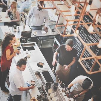 Grupo de gente diversa que ordena la cafetería del café