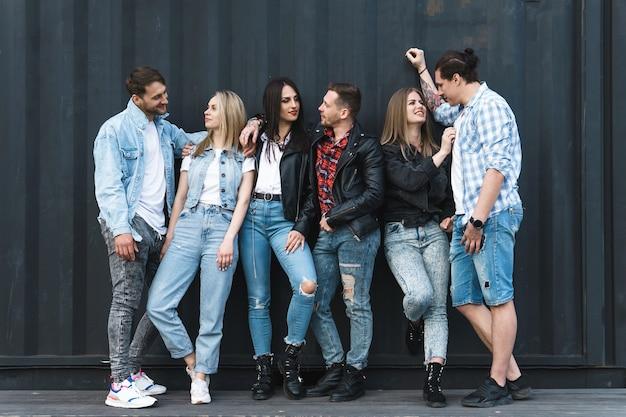 Grupo de gente joven y elegante durante una reunión en una calle de la ciudad
