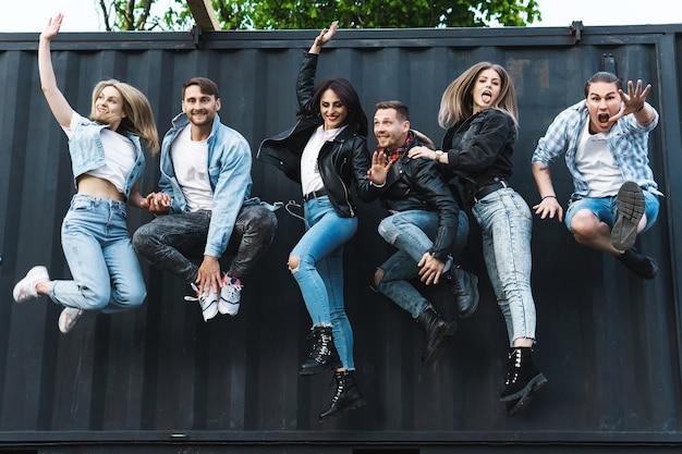 Grupo de gente joven y elegante saltando en el aire en una calle de la ciudad