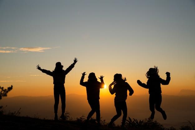 Grupo de gente joven feliz que salta en la colina. mujeres jóvenes disfrutando