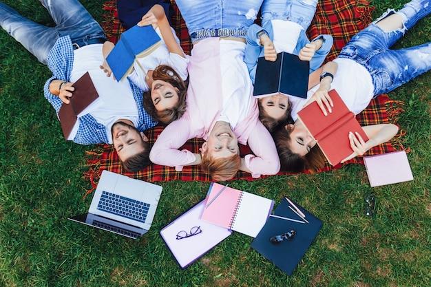 Un grupo de gente joven hermosa yace en la hierba. los estudiantes se relajan después de las clases en el campus.