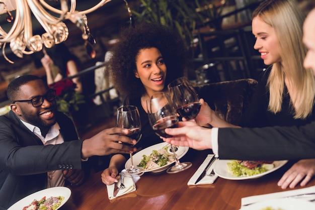Grupo de gente joven que bebe el vino en un restaurante.