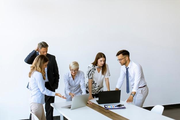 Grupo de gente de negocios con adultos jóvenes y colega senior en reunión en el interior de la oficina moderna y luminosa