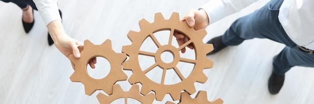 Grupo de gente de negocios apilando engranajes de madera vista superior concepto de trabajo en equipo