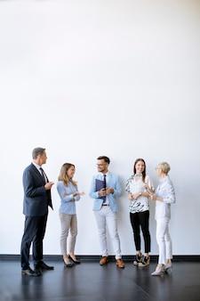 Grupo de gente de negocios de pie junto a la pared en la oficina