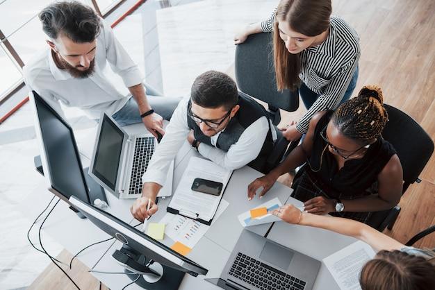 Un grupo de gente ocupada multinacional que trabaja en la oficina.