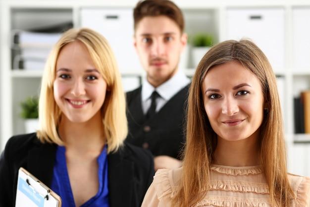 El grupo de gente sonriente se coloca en la oficina que mira en retrato de la cámara. proyecto de solución de mediación de energía de cuello blanco asesor creativo participación profesión tren banco abogado cliente visita concepto