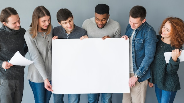 Grupo de gente sujetando plantilla de papel en blanco