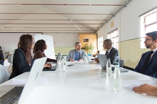 Grupo de gerentes ocupados durante la sesión informativa de la mañana