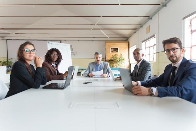 Grupo de gerentes serios durante la sesión informativa matutina