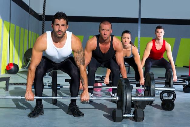 Grupo de gimnasia con barra de levantamiento de pesas, entrenamiento crossfit.