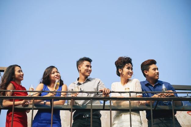 Grupo de glamorosos invitados de fiesta asiáticos apoyándose en la barandilla y mirando a otro lado