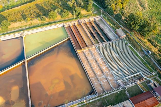 Un grupo de grandes tanques de sedimentación. deposición de agua, limpieza en un depósito con organismos biológicos en una estación de agua. diferente grado de tratamiento de aguas residuales