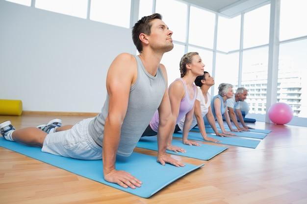 Grupo haciendo pose de cobra en fila en la clase de yoga