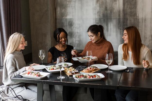 Grupo de hermosas mujeres jóvenes disfrutando de una cena juntos