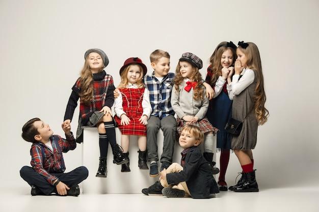 El grupo de hermosas niñas y niños en una pared en colores pastel