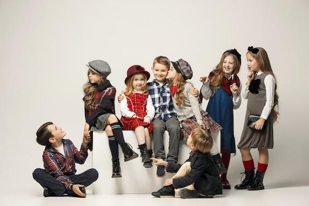 El grupo de hermosas niñas y niños en un pastel.