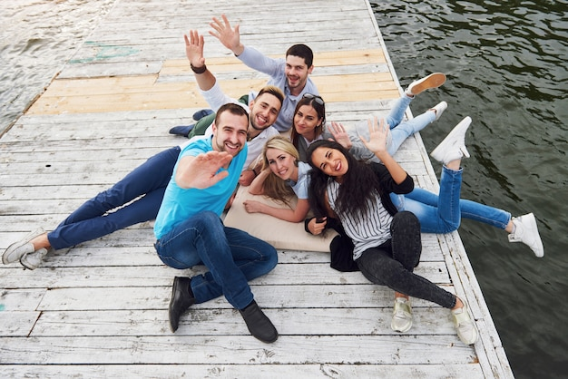 Grupo de hermosos jóvenes en el muelle, la satisfacción de los amigos crea vida emocional.