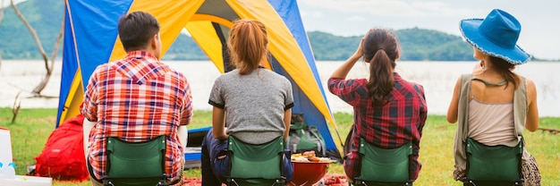 Grupo de hombre y mujer disfrutar de picnic y barbacoa de camping en el lago con tiendas de campaña en el fondo. joven mujer de raza mixta asiática y el hombre. bandera panorámica.