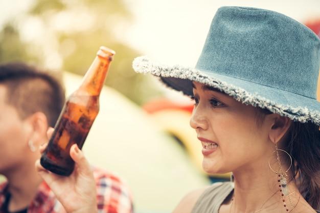 Grupo de hombre y mujer disfrutar de picnic y barbacoa de camping en el lago con tiendas de campaña en el fondo. joven mujer de raza mixta asiática y el hombre. las manos de los jóvenes tostando y animando la cerveza. imagen filtrada vintage