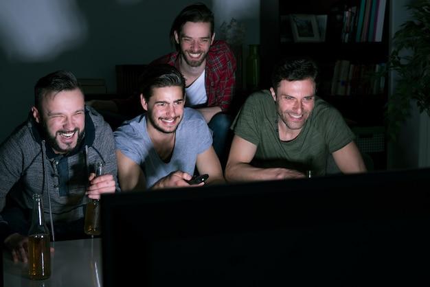 Grupo de hombres bebiendo cerveza y viendo fútbol en la televisión