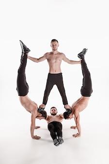 El grupo de hombres caucásicos acrobáticos gimnásticos en pose de equilibrio