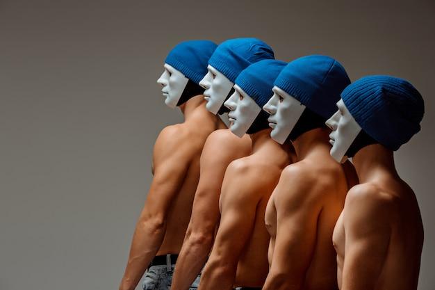 El grupo de hombres caucásicos con máscaras blancas y sombreros, jeans