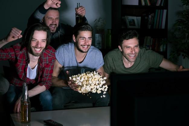 Grupo de hombres comiendo palomitas de maíz y viendo fútbol en la televisión