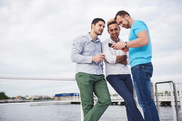 Un grupo de hombres jóvenes y felices en el muelle.