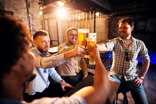 Grupo de hombres jóvenes positivos que tuestan con una cerveza en el pub soleado después del trabajo.