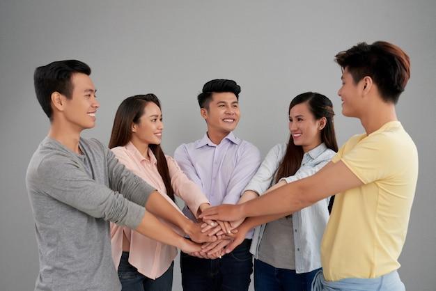 Grupo de hombres y mujeres asiáticos posando y uniendo manos