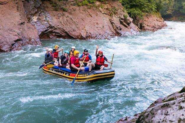 Grupo de hombres y mujeres están haciendo rafting en el río, deporte extremo y divertido