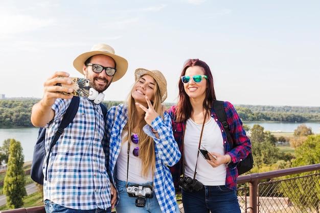 Grupo de hombres y mujeres excursionistas tomando selfie en teléfono móvil