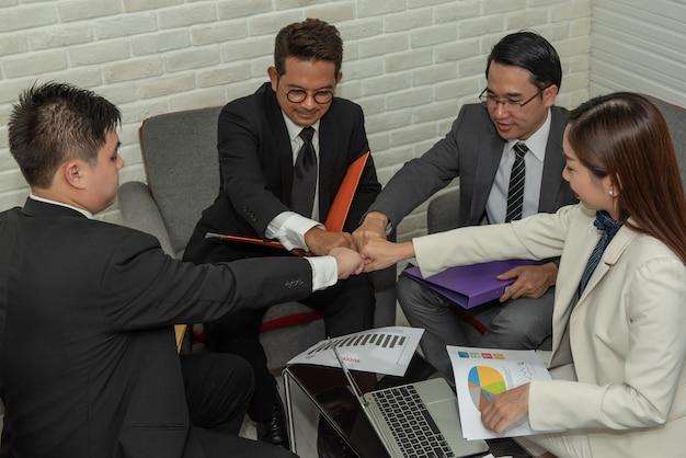 El grupo de hombres de negocios asiáticos da hacer gesto del topetón del puño junto en trabajo en equipo.