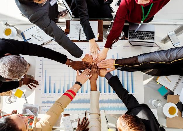 Un grupo de hombres de negocios internacionales están juntando sus manos