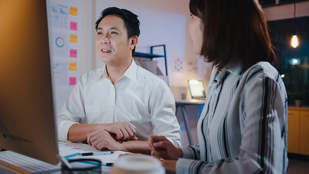 Grupo de hombres de negocios y mujeres de negocios de asia utilizando presentación de computadora y reunión de comunicación para intercambiar ideas