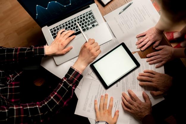 Grupo de hombres de negocios que tienen una sesión informativa delante de la computadora portátil
